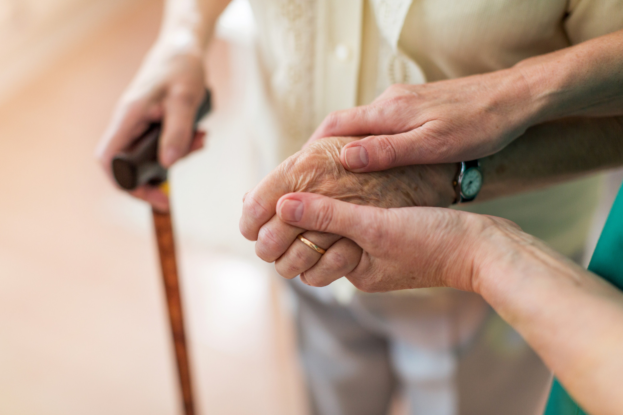 Helping hands: carer looks after old woman with walking stick
