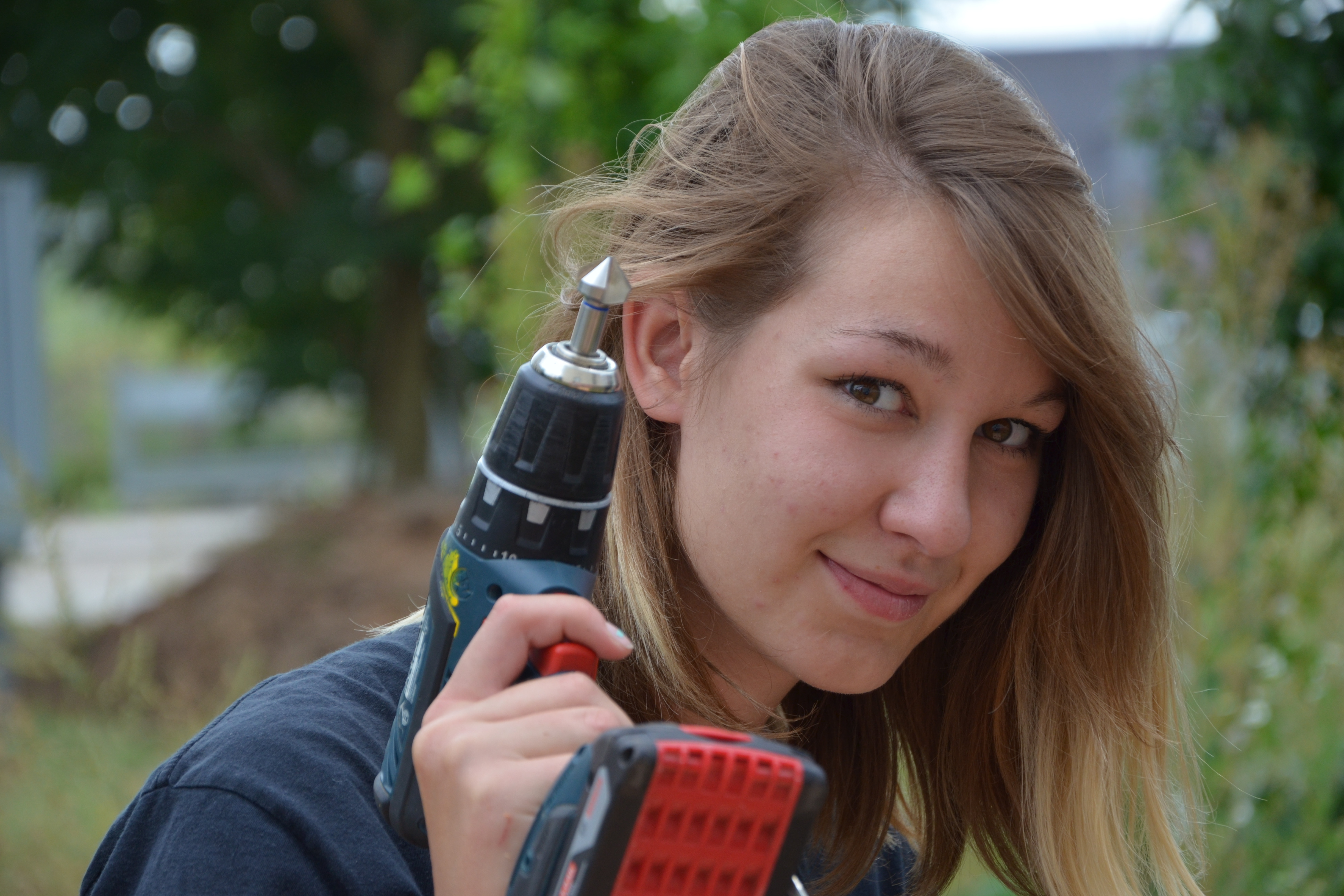 Girl with cordless screwdriver in her hand